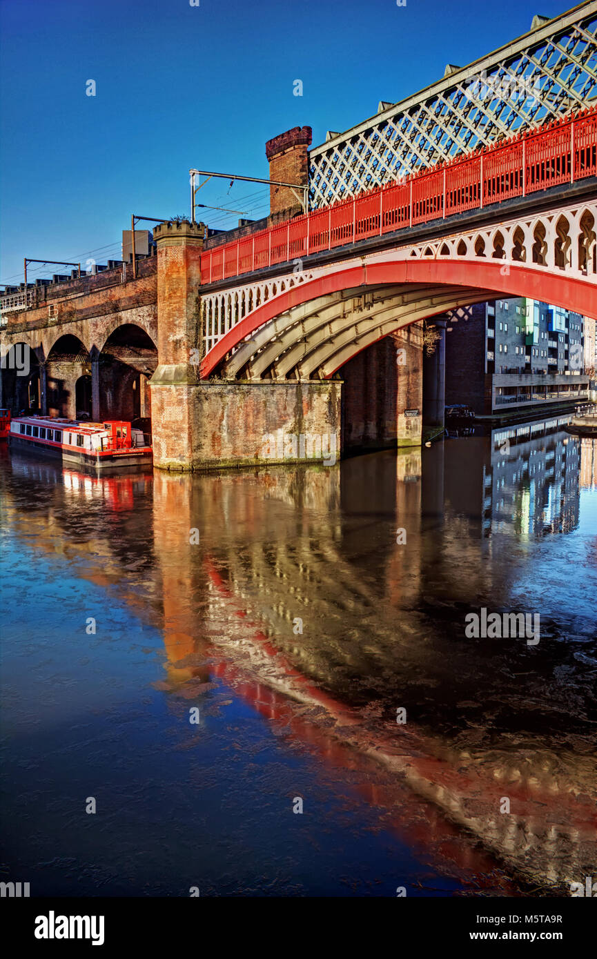 Portrait of a Castlefield bridge, with the canal water flowing under the bridge in Manchester - Stock Image