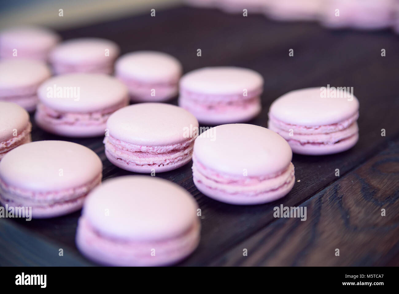 Pink macarons on wooden table - Stock Image