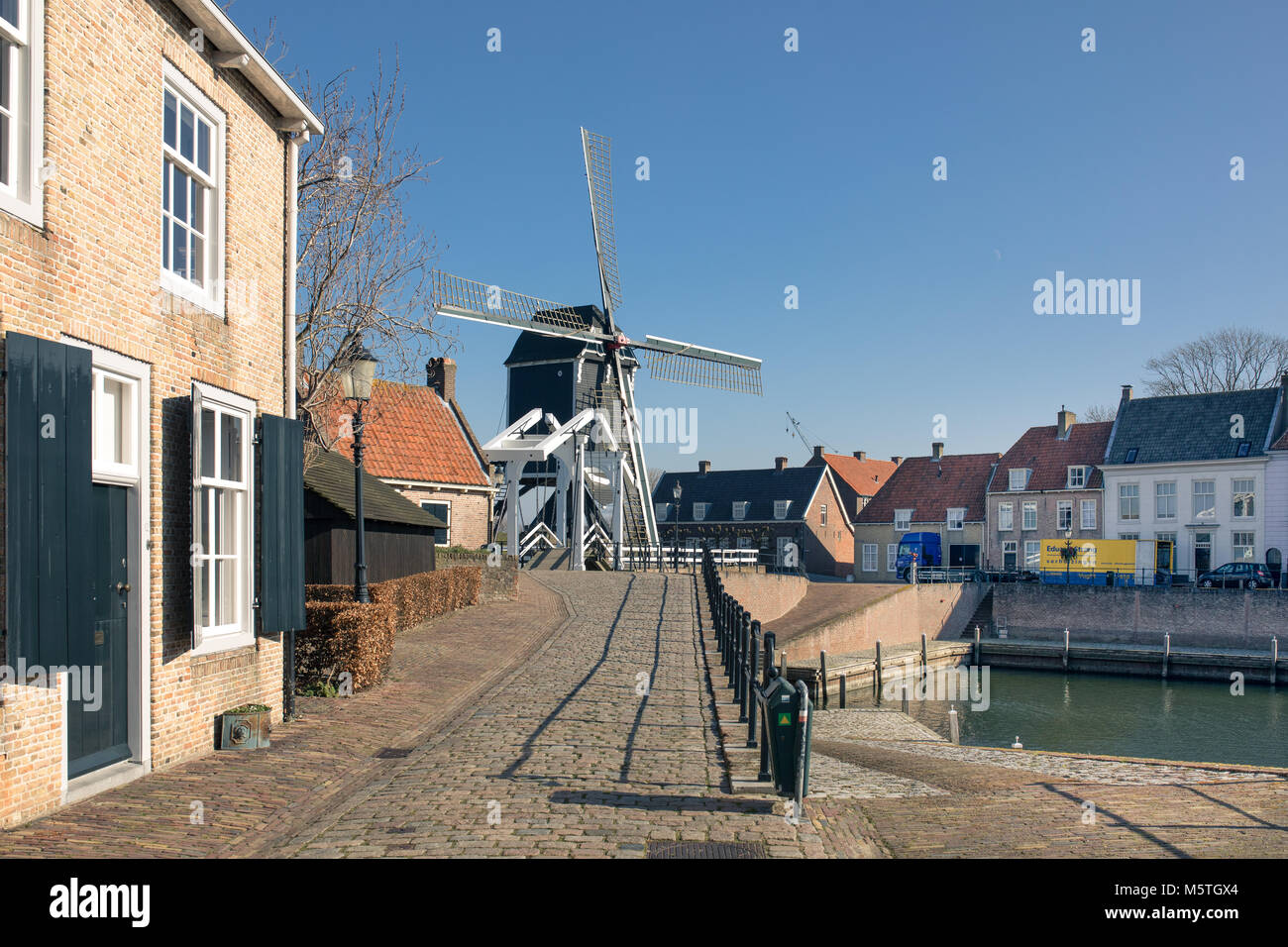 Heusden, Holland, cityscape with a harbour, a quay and an old, vintage, wooden windmill - Stock Image