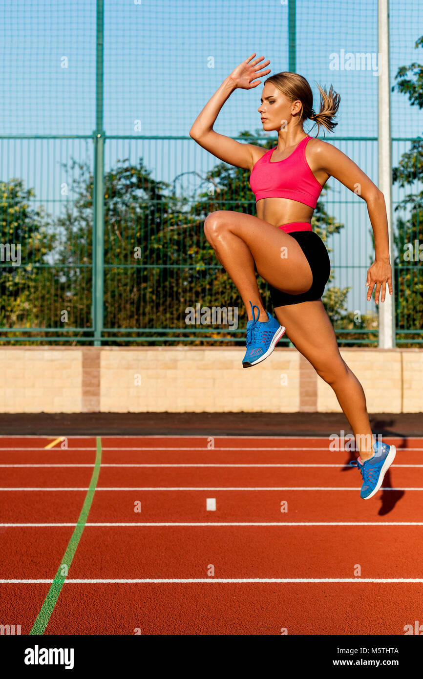 Young, beautiful girl athlete in sportswear doing warm-up at the stadium. Jumping up, one leg bent at the knee - Stock Image
