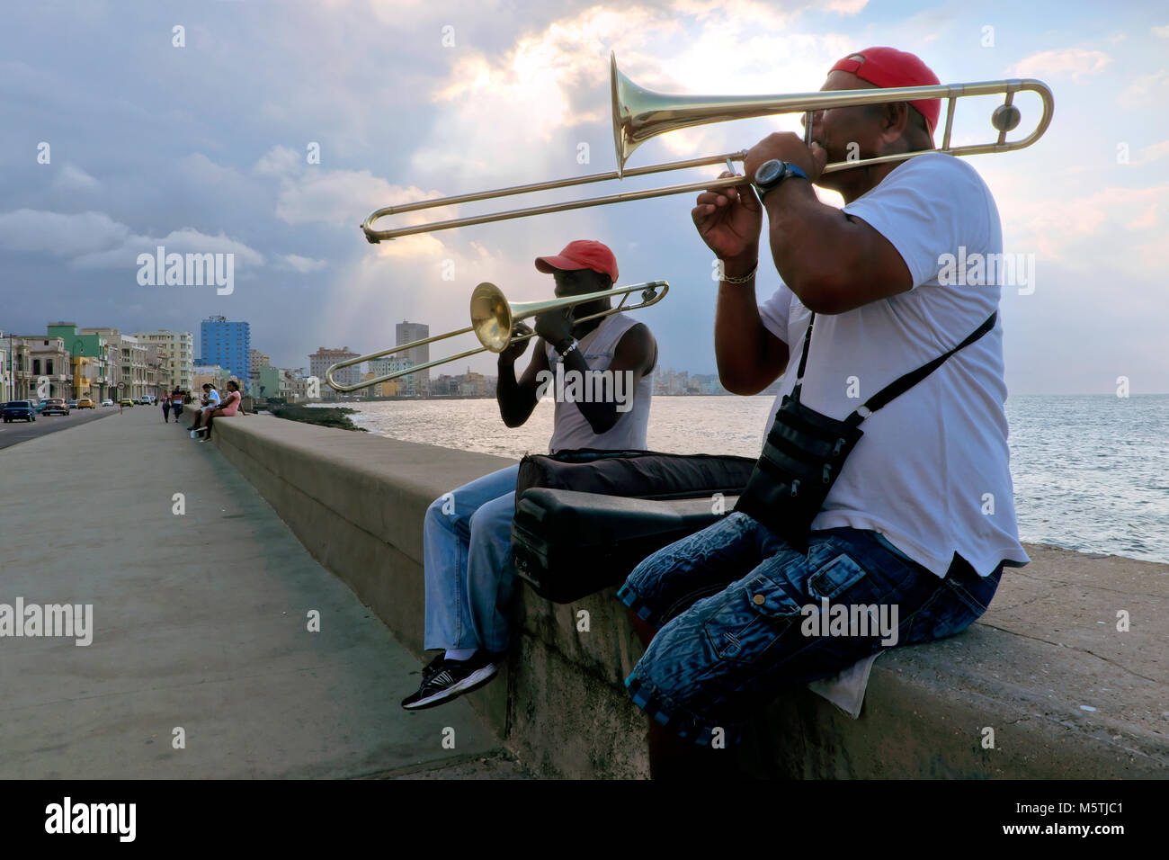 Trombone buskers / musicians playing along the Malecón Esplanade, Havana, Cuba - Stock Image