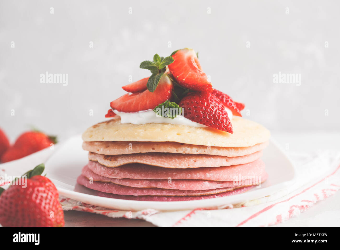 Stack of pink ombre  pancakes with strawberry. Breakfast background, copy space. - Stock Image