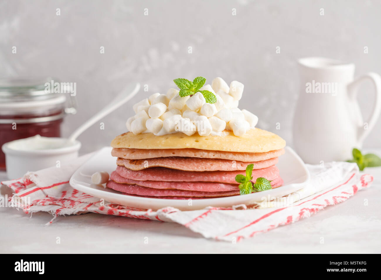 Stack of pink ombre  pancakes with marshmallow. Breakfast background, copy space. - Stock Image