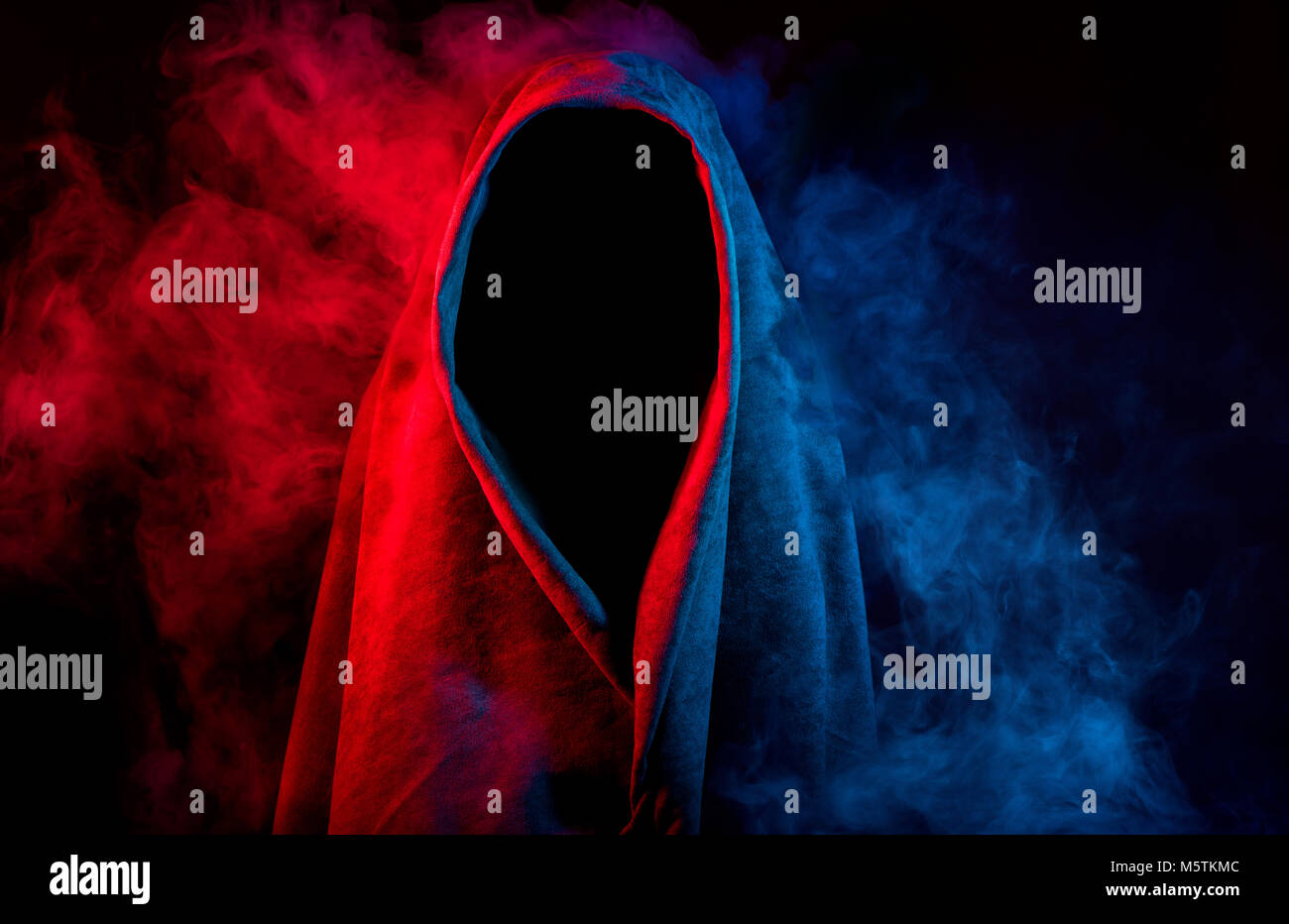 mysterious dark silhouette in hood hidden by colorful smoke on black background Stock Photo