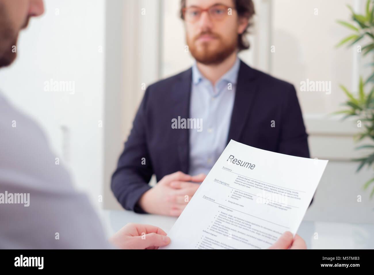 Recruiter reading curriculum during job interview - Stock Image