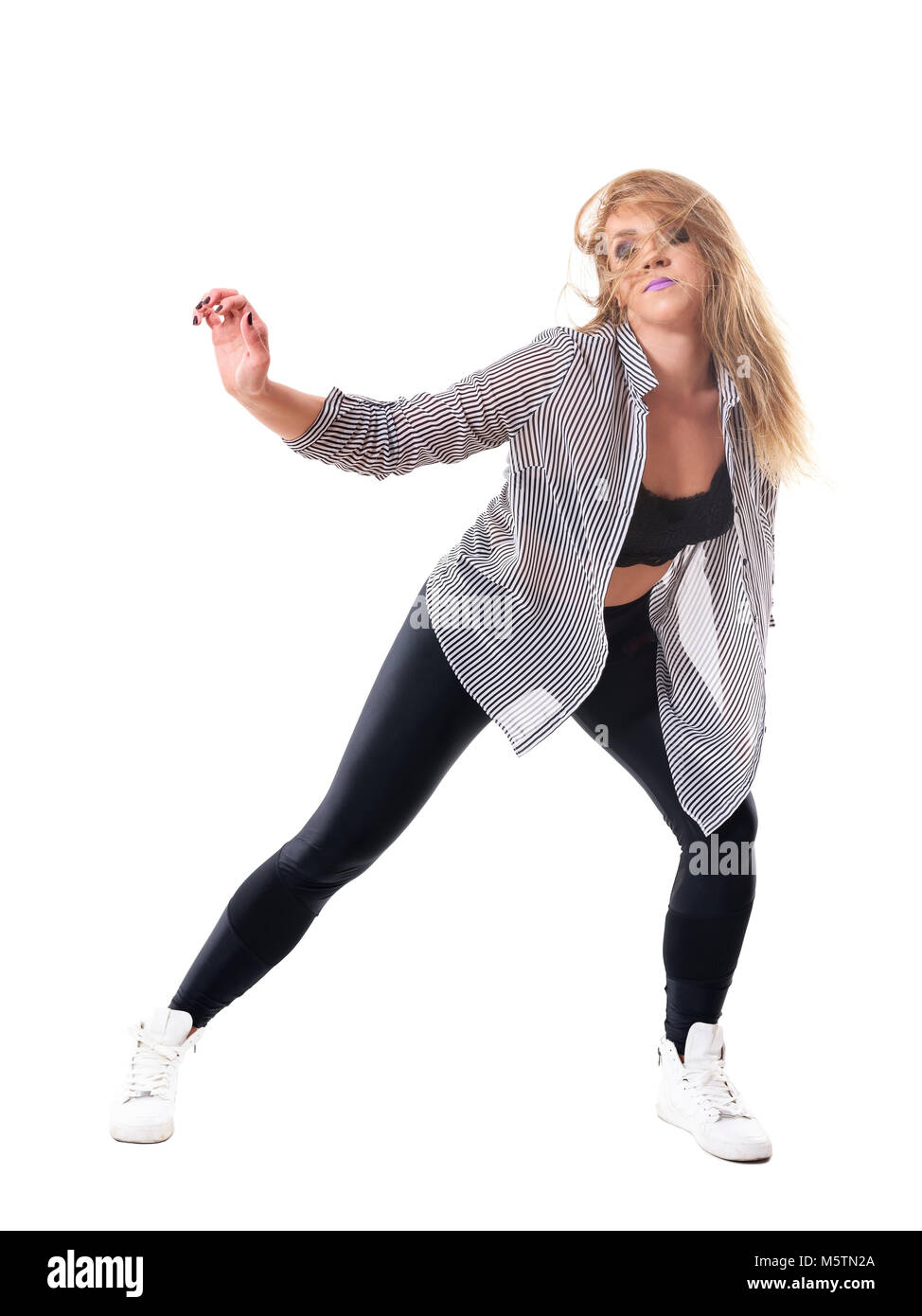 Energetic passionate female dancer in striped shirt with tousled hair and closed eyes. Full body length portrait - Stock Image