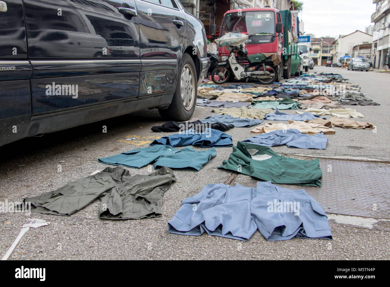 PENANG, MALAYSIA, NOV 12 2017, Short pants lying on the asphalt road. Drying clothes on the street of the city. Stock Photo