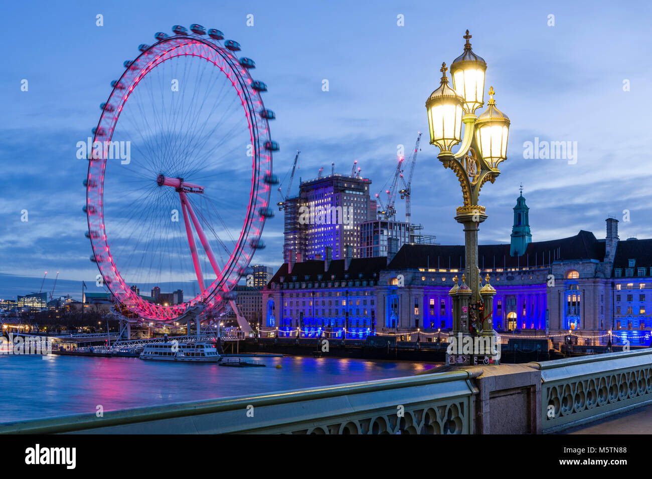 The London Eye and County Hall at dawn viewed from Westminster Bridge - Stock Image