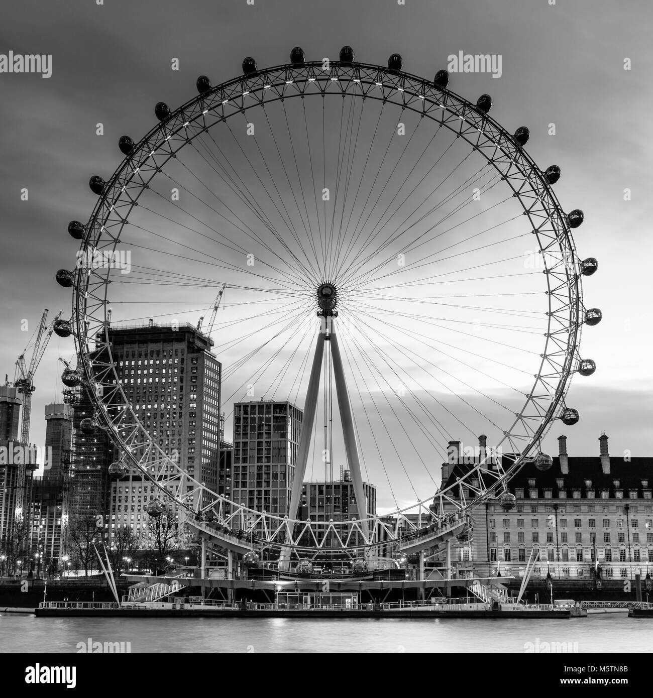 Black and White image of The London Eye and County Hall at dawn - Stock Image
