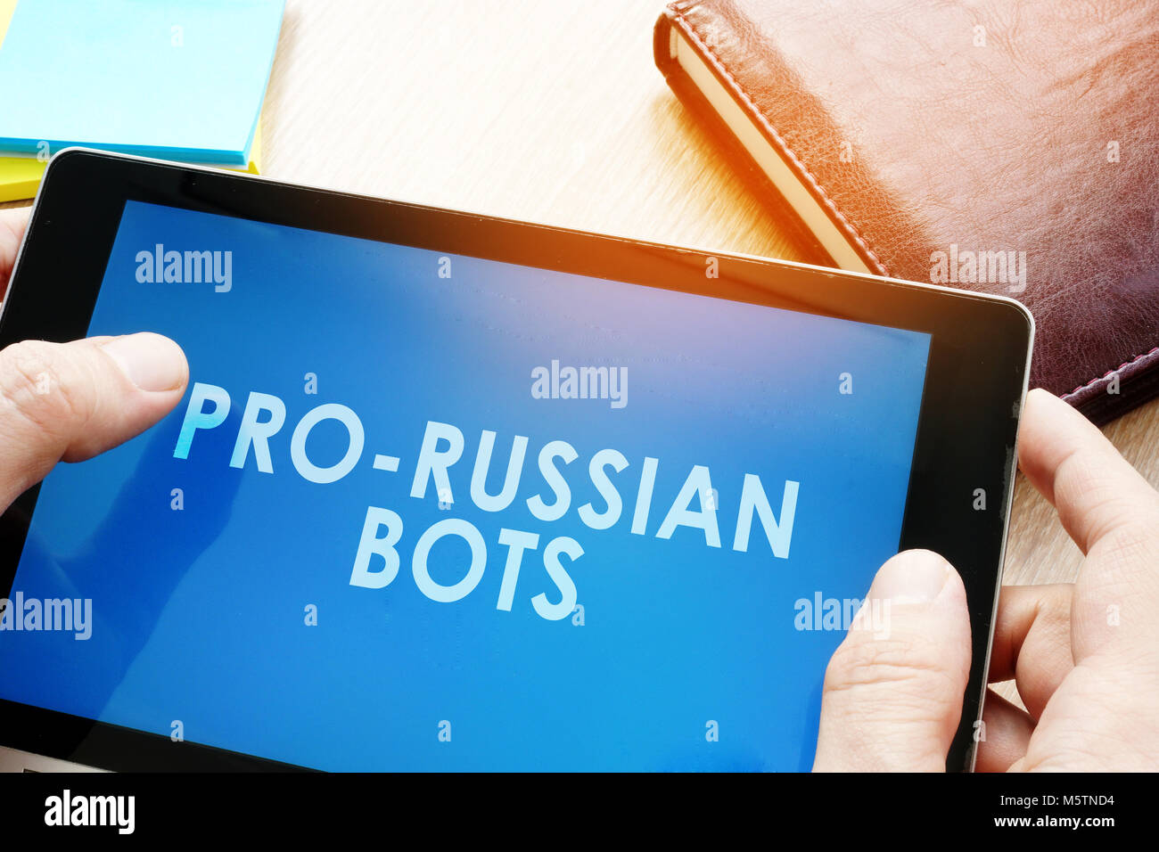 Man holding tablet with words pro-russian bots. Russian internet propaganda concept. - Stock Image