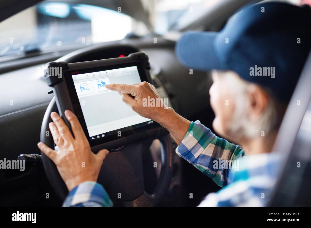 Senior female mechanic repairing a car in a garage. - Stock Image