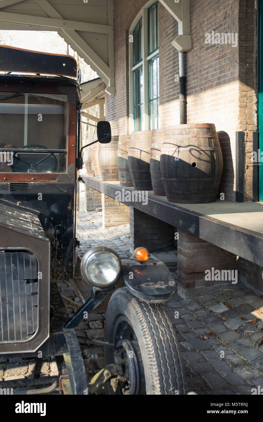 Vintage, retro car by a loading platform, ramp. Wooden whisky barrels in the background, mafia and prohibition times - Stock Image