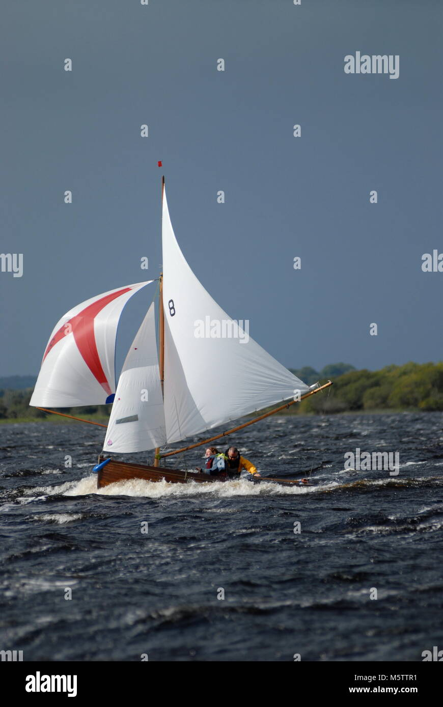 A traditional Water Wag dinghy races down Lough Ree during the Irish sailing raid on the Shannon River in Ireland. Stock Photo