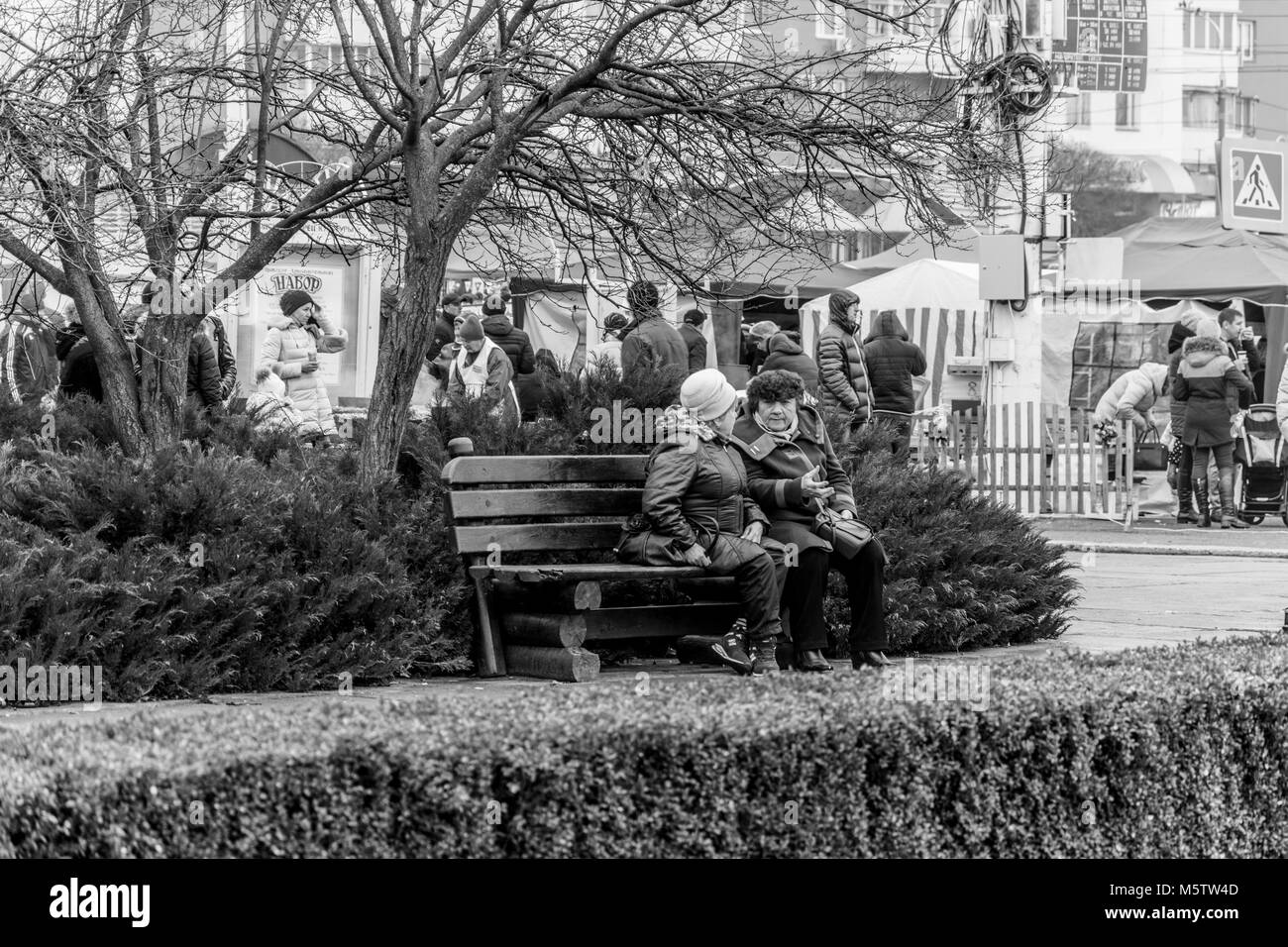 Elderly women talking on the bench, black and white reportage photo - Stock Image