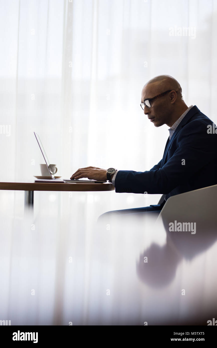 Male office worker using laptop at office. Side view of business man sitting at table and working on laptop. - Stock Image