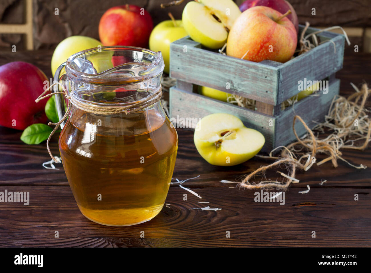 Fresh fruity apple juice and ripe apples on a wooden table. The concept of nutrition for superfoods and health or - Stock Image