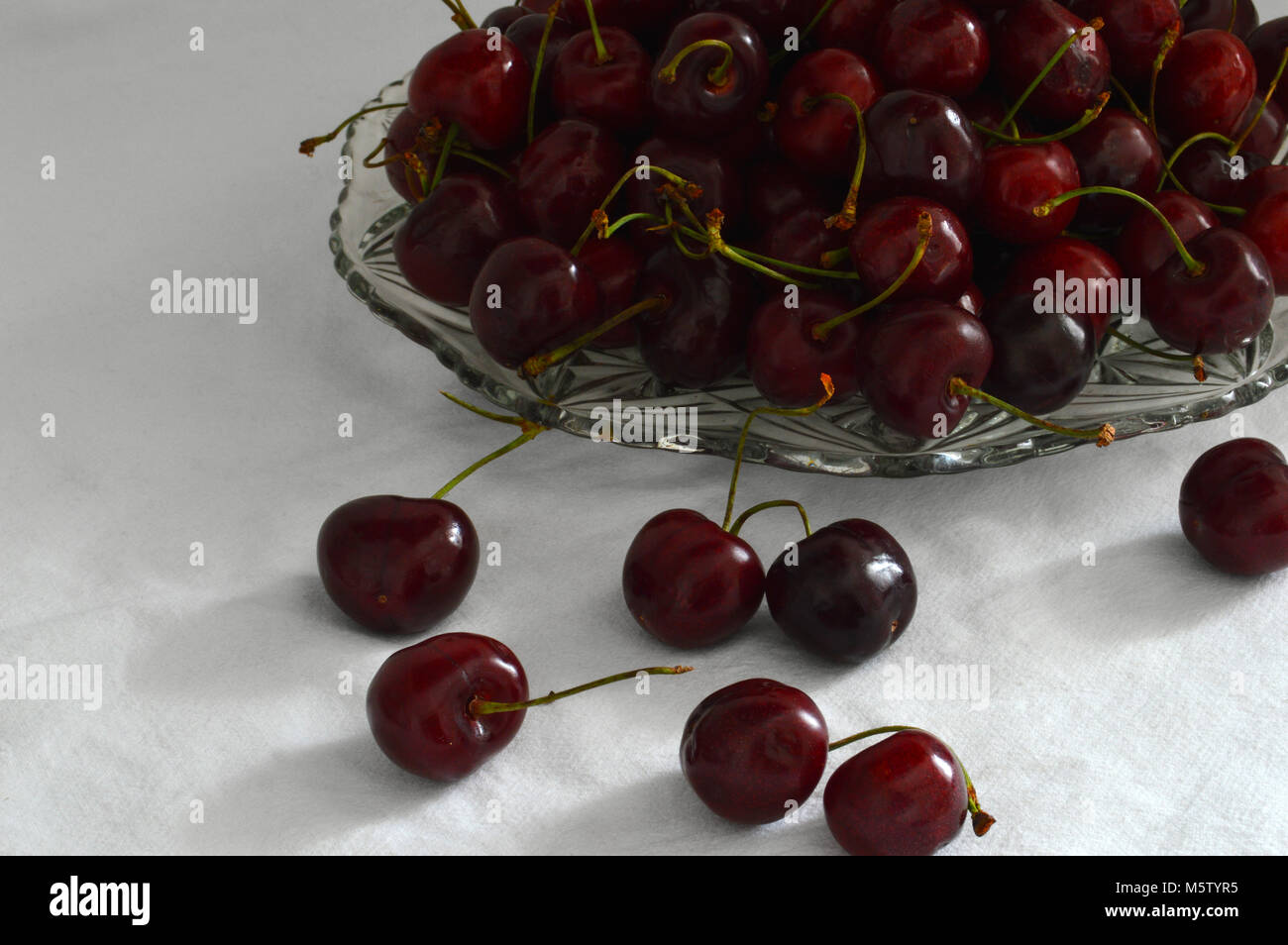 still life with a glass plate with red cherries on white background - Stock Image