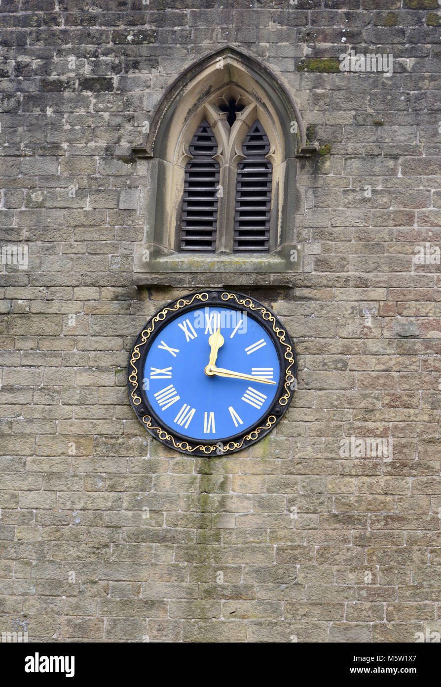 The blue clock face set in the stone tower of St Martin's Church shows quarter past twelve. Stoney Middleton, - Stock Image