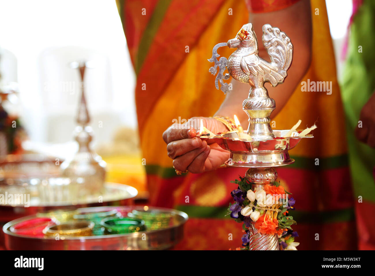 Closeup shot on Hindu wedding rituals Traditional south Indian brass oil lamp also Red Carpet - Stock Image