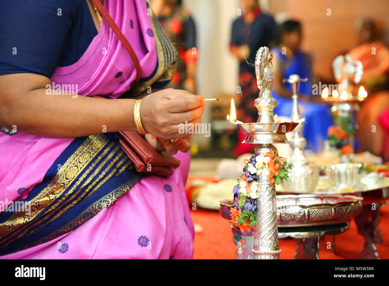 Traditional south Indian brass oil lamp with peoples - Stock Image