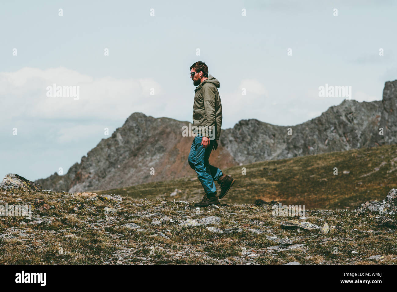 Man walking alone in scandinavian mountains Travel Lifestyle concept traveler outdoor wild nature - Stock Image