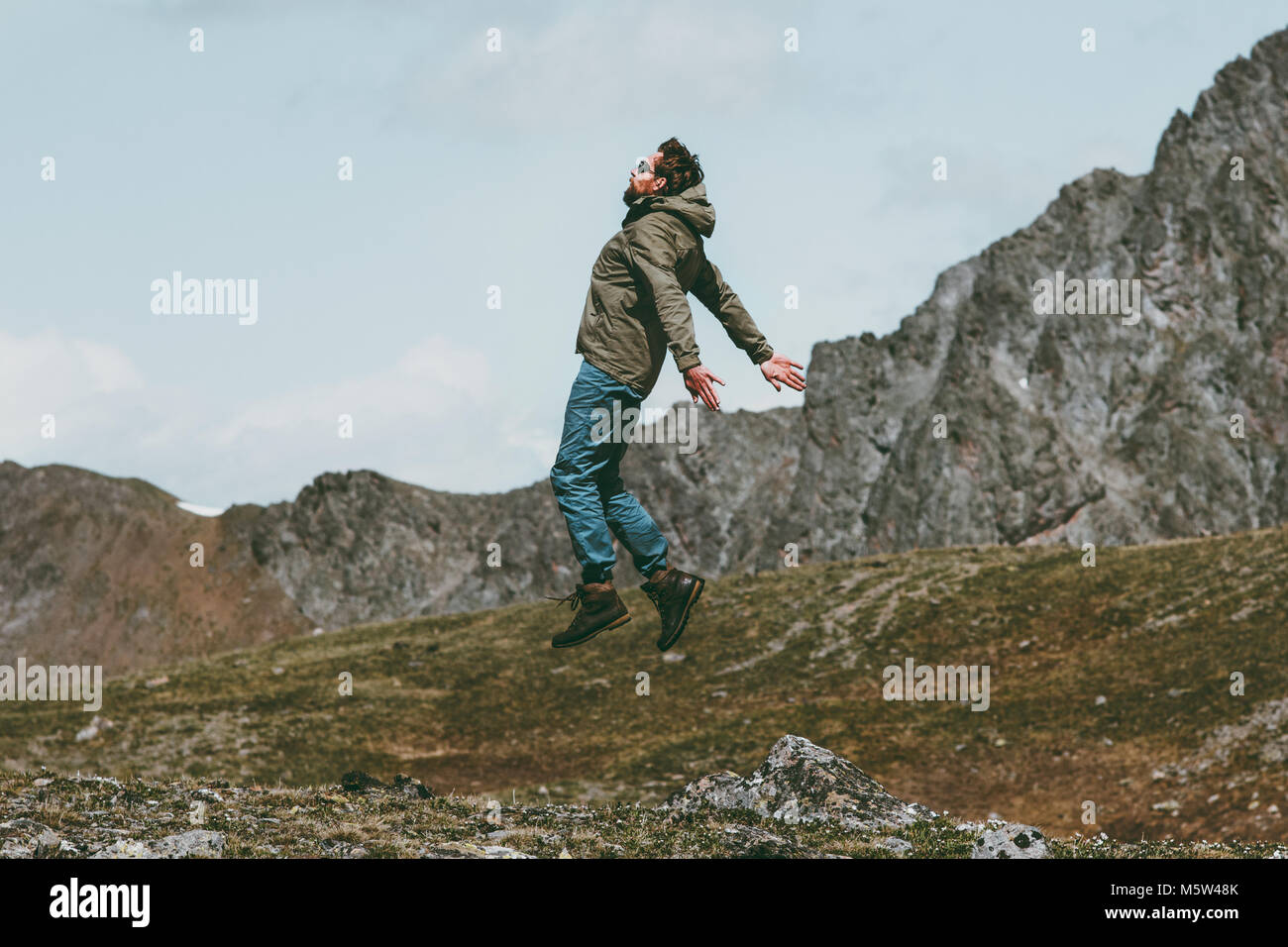 Travel Man jumping levitation outdoor on mountains lifestyle spiritual concept - Stock Image