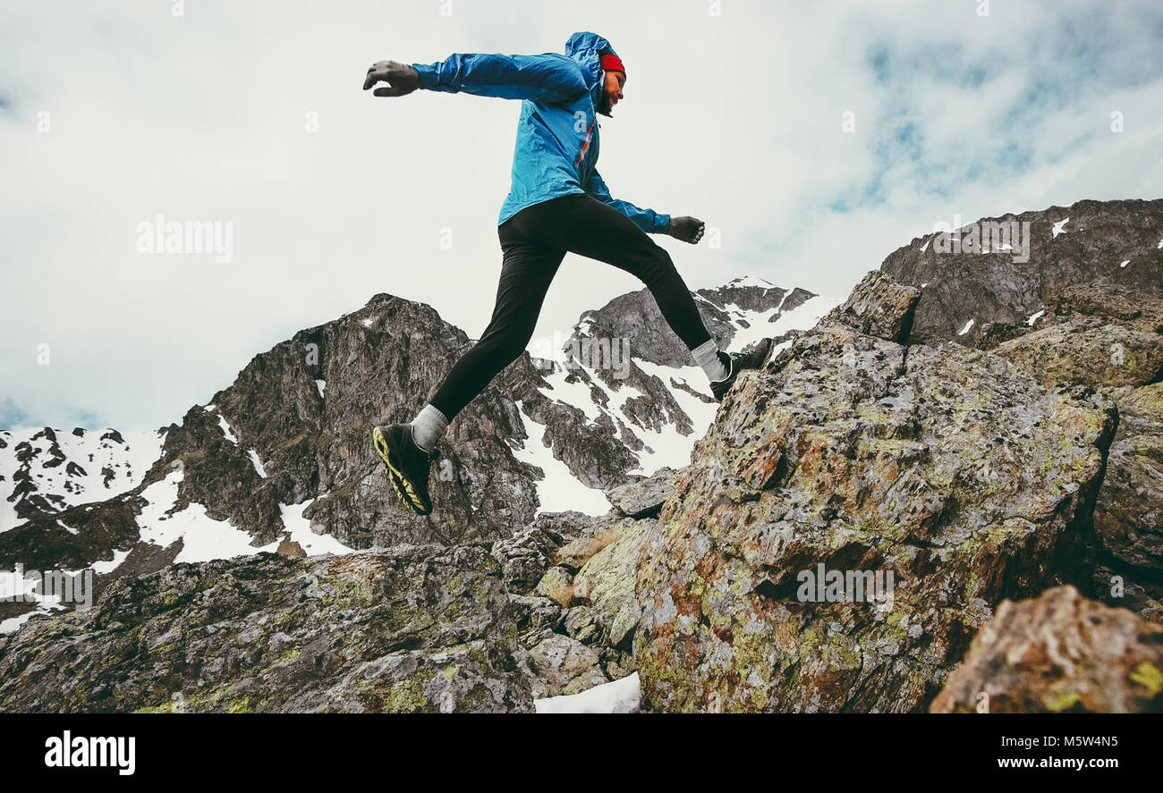 Travel Man running in mountains adventure lifestyle endurance concept active vacations skyrunning sport - Stock Image