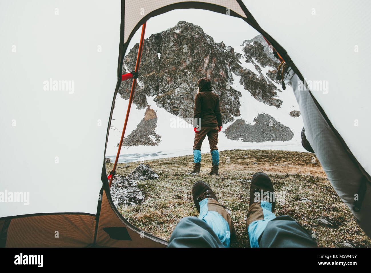 Camping traveling couple view from tent entrance woman walking in mountains man feet relaxing inside Lifestyle concept - Stock Image