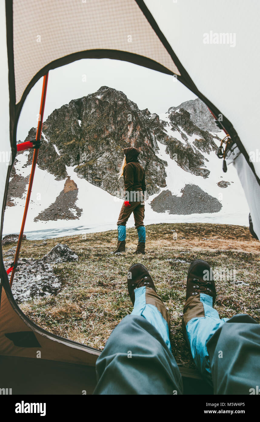 Travel lifestyle camping couple view from tent entrance woman walking in mountains man feet relaxing inside adventure - Stock Image