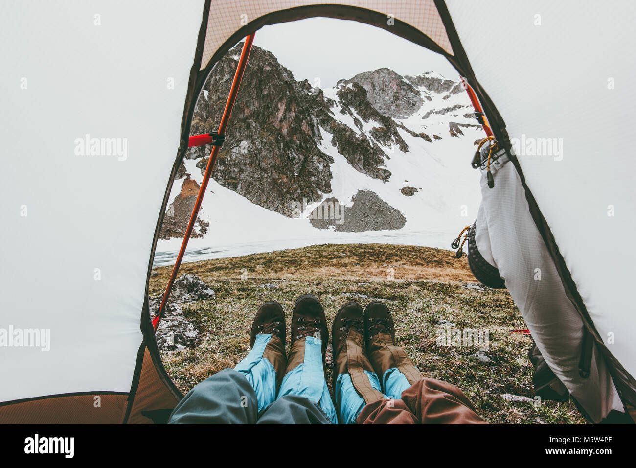 Travel couple feet mountains view from tent camping entrance Lifestyle concept adventure vacations outdoor - Stock Image