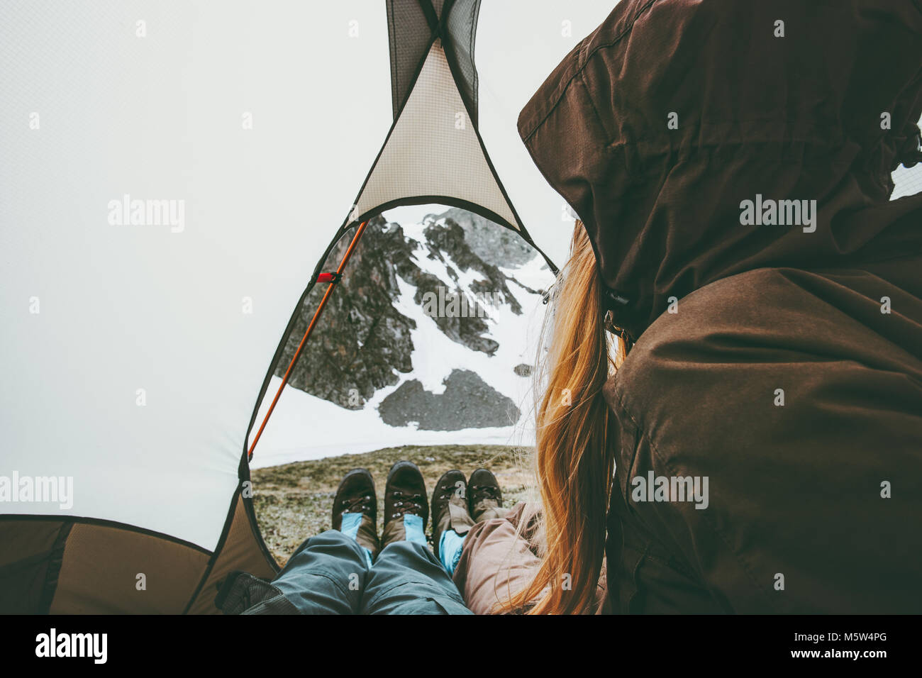 Travel couple in tent camping relaxing inside Lifestyle concept adventure vacations outdoor - Stock Image