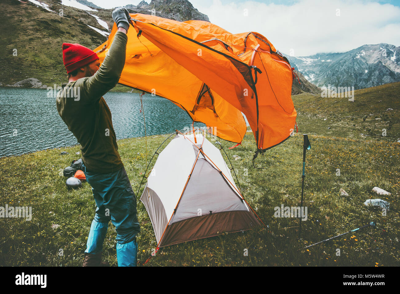 Man Traveler pitching tent camping gear outdoor Travel adventure lifestyle concept summer journey vacations in mountains - Stock Image