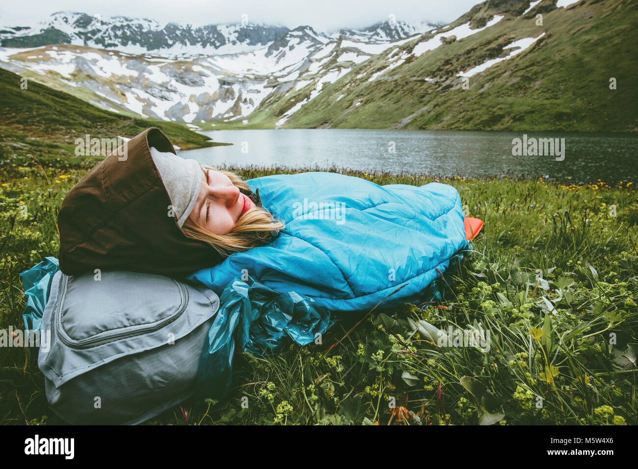 Woman relaxing in sleeping bag laying on grass enjoying lake and mountains landscape Travel Lifestyle camping concept - Stock Image