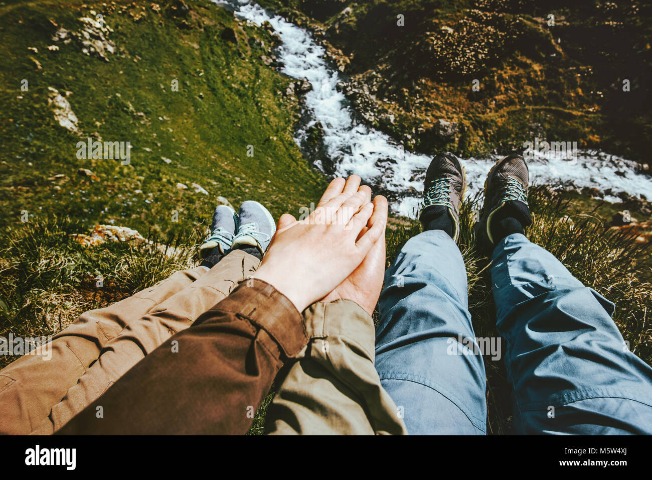 Couple in love holding hands relaxing together on mountain summit Travel happy emotions Lifestyle concept adventure - Stock Image