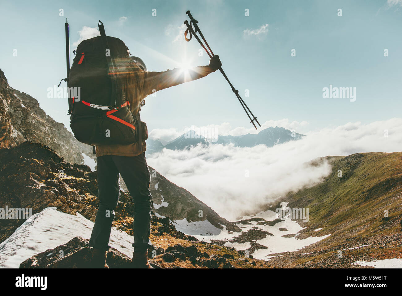 Backpacker Man on mountain summit Travel success lifestyle survival concept adventure outdoor active vacations sunny - Stock Image