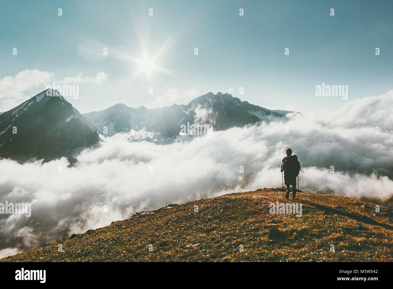 Traveler hiking in mountains clouds landscape Travel lifestyle adventure concept summer vacations outdoor - Stock Image