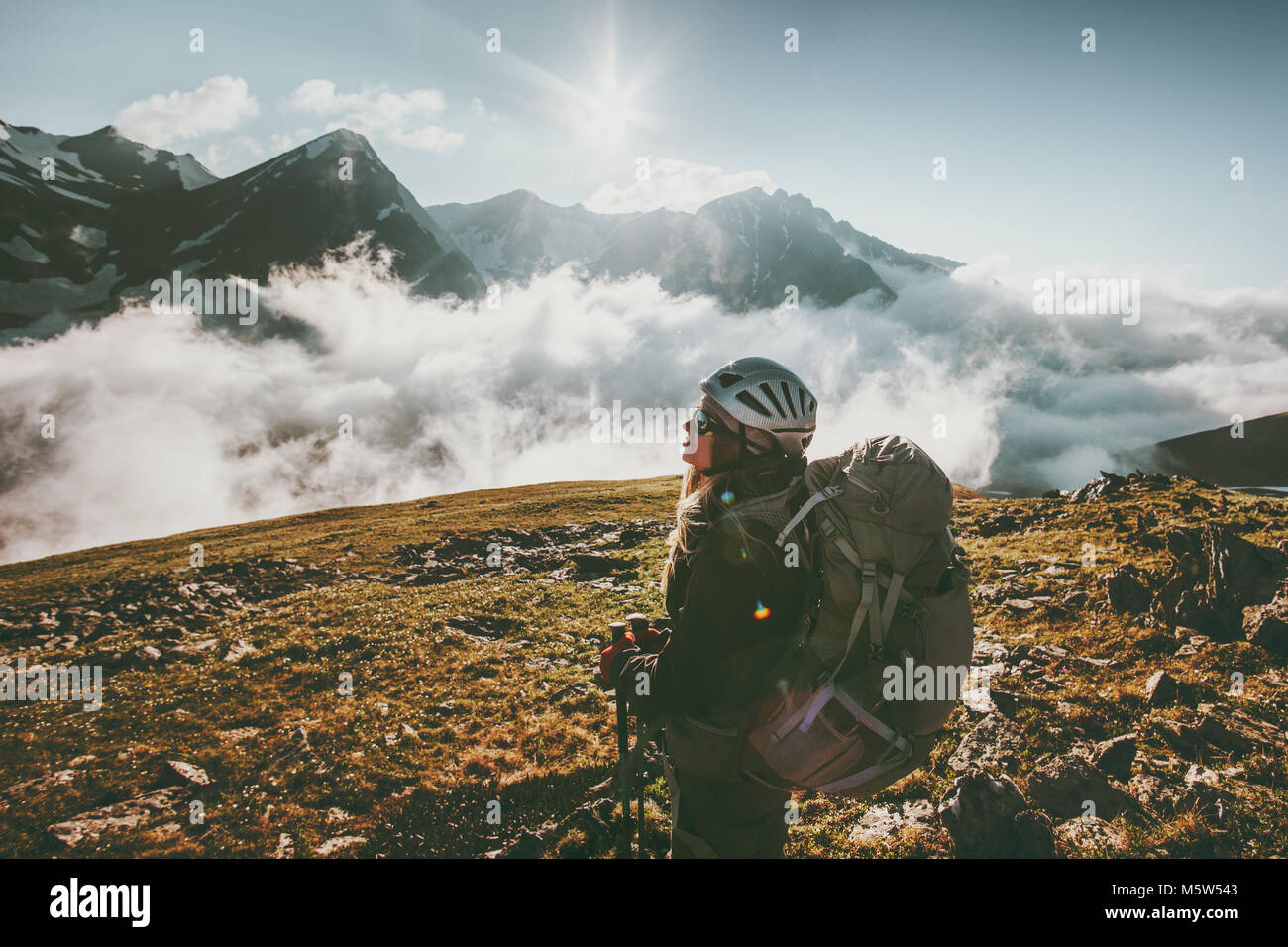 Backpacker woman observing mountains clouds landscape Travel healthy lifestyle adventure concept active summer vacations - Stock Image