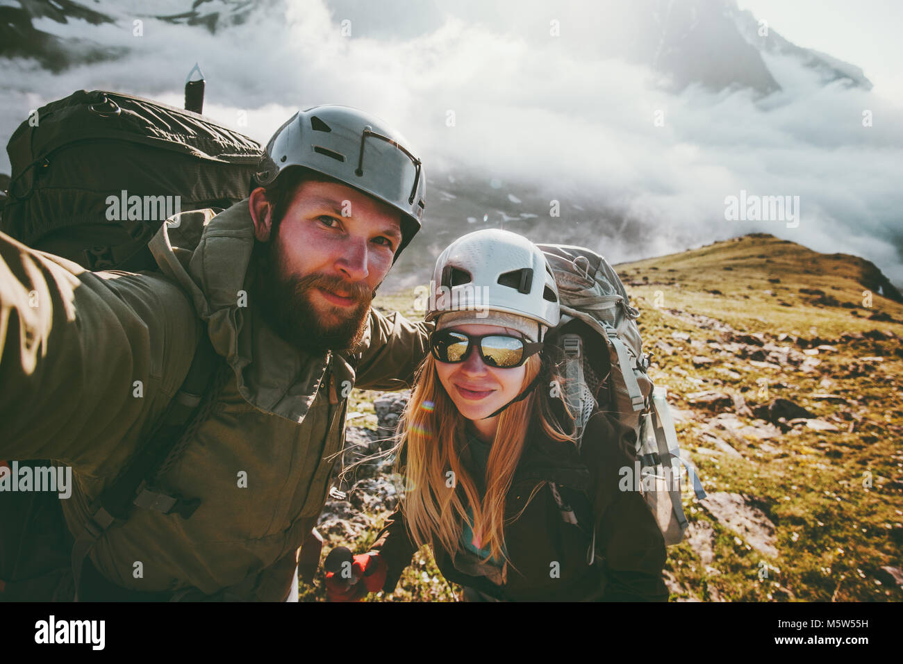 Couple travel selfie man and woman hiking in mountains love and adventure Lifestyle wanderlust concept - Stock Image