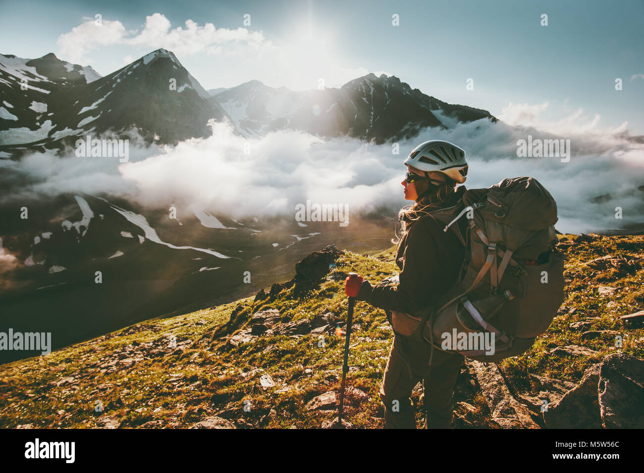 Backpacker woman enjoying mountains clouds landscape Travel lifestyle adventure concept active summer vacations - Stock Image