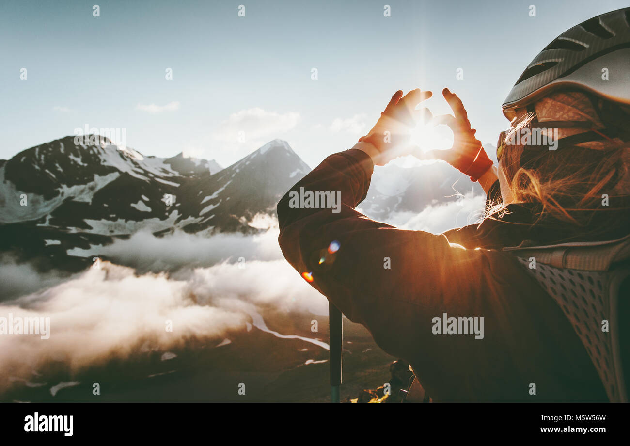 Woman hands Heart symbol shaped Travel Lifestyle and Feelings concept with sunset mountains on background - Stock Image