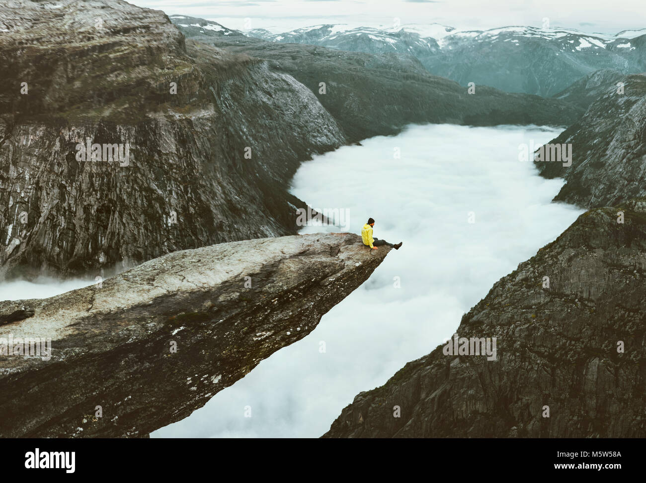 Man traveler on Trolltunga rocky cliff edge in Norway mountains Travel Lifestyle adventure emotional concept extreme - Stock Image