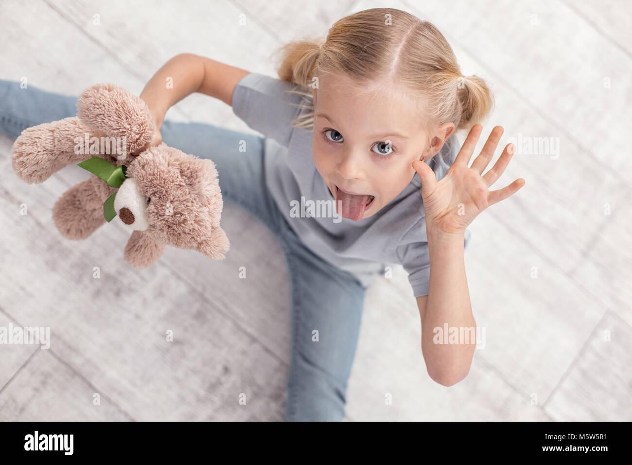 Funny irresistible girl showing tongue - Stock Image