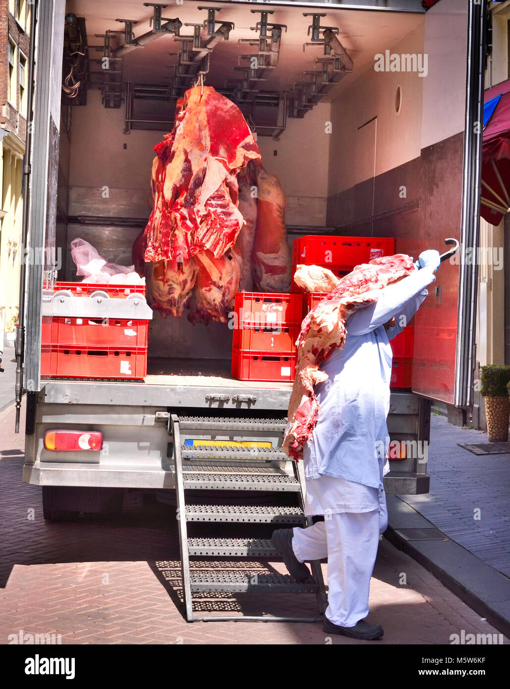 Food delivery of raw beef or pork, half beef in a cooling truck. Fresh red meat, buttery or slaughter house theme. - Stock Image