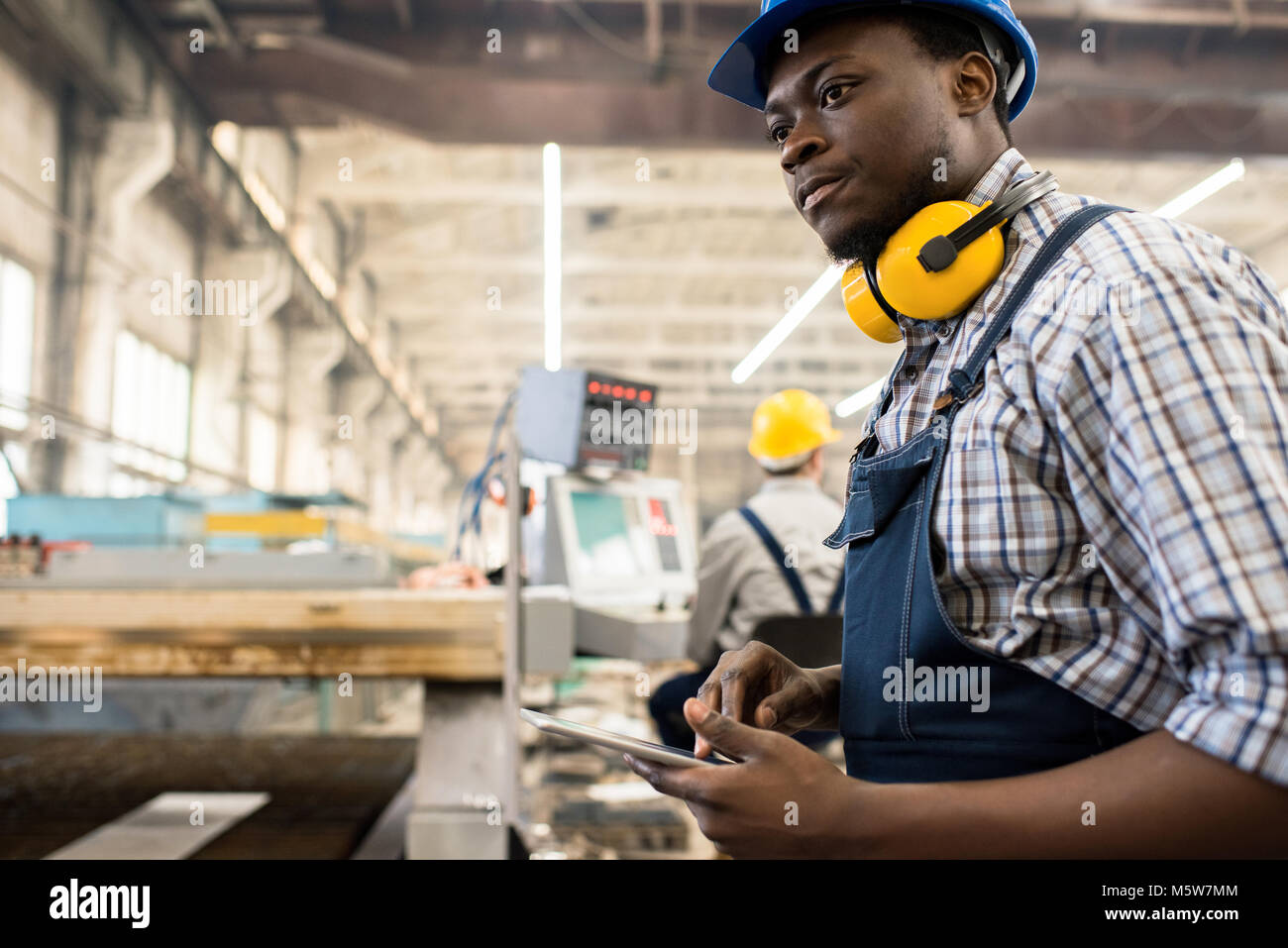 Concentrated African American worker wearing overall and hardhat operating machine with help of digital tablet, - Stock Image
