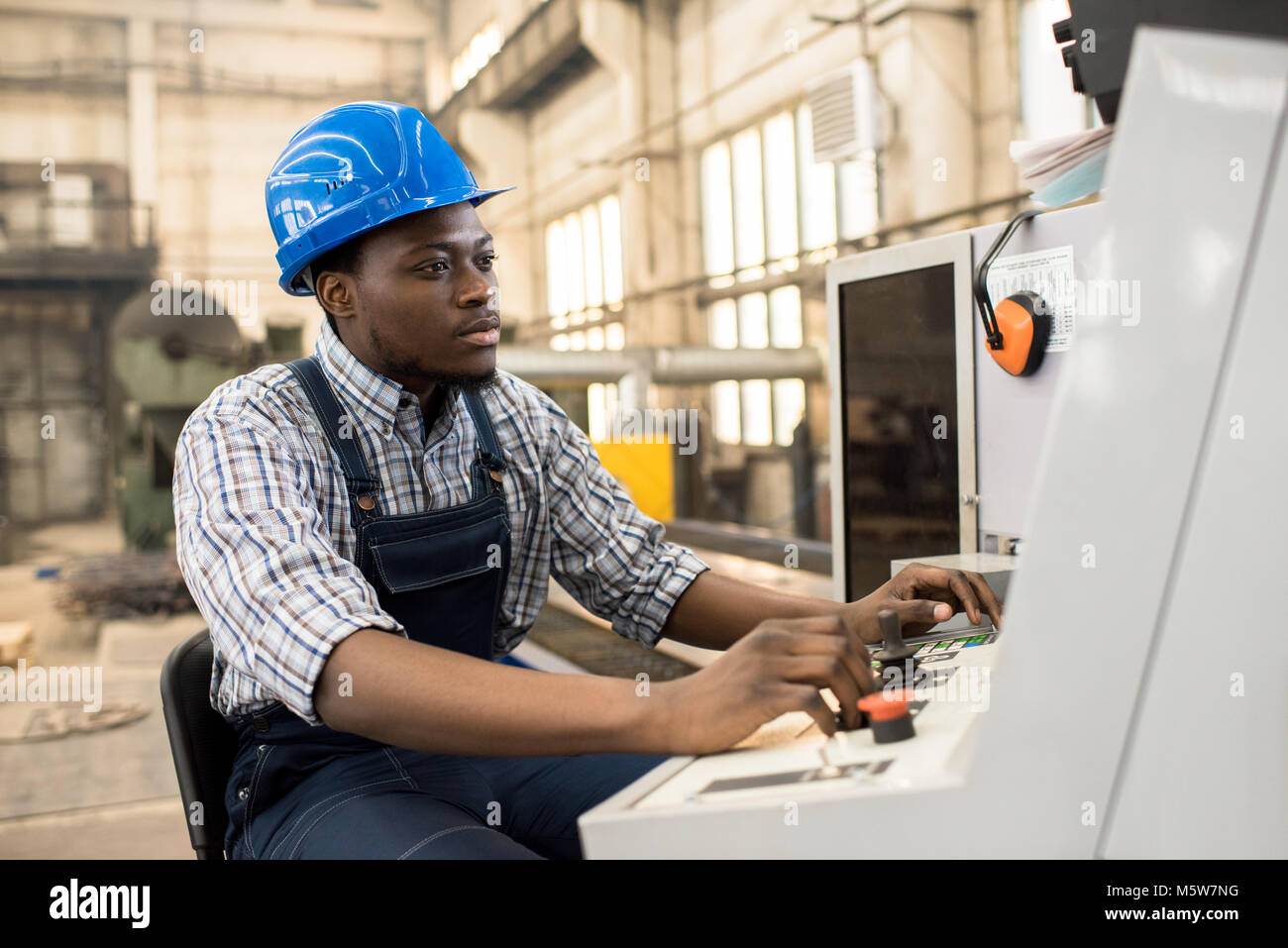 Portrait shot of highly professional worker wearing checked shirt and overall operating machine at production department - Stock Image