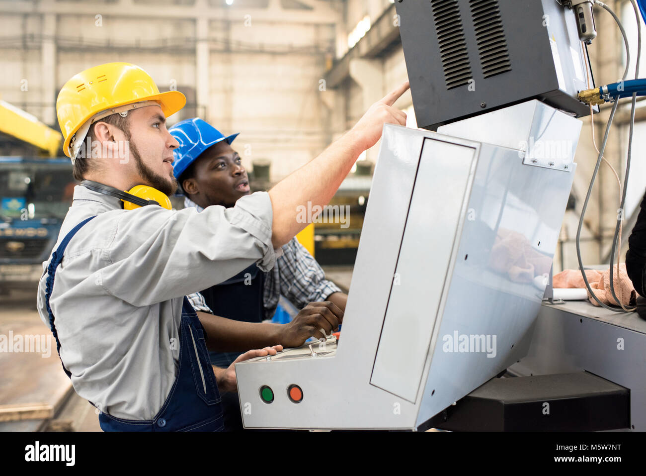 Multi-ethnic team of machine operators wearing hardhats and overalls discussing working process while standing in - Stock Image
