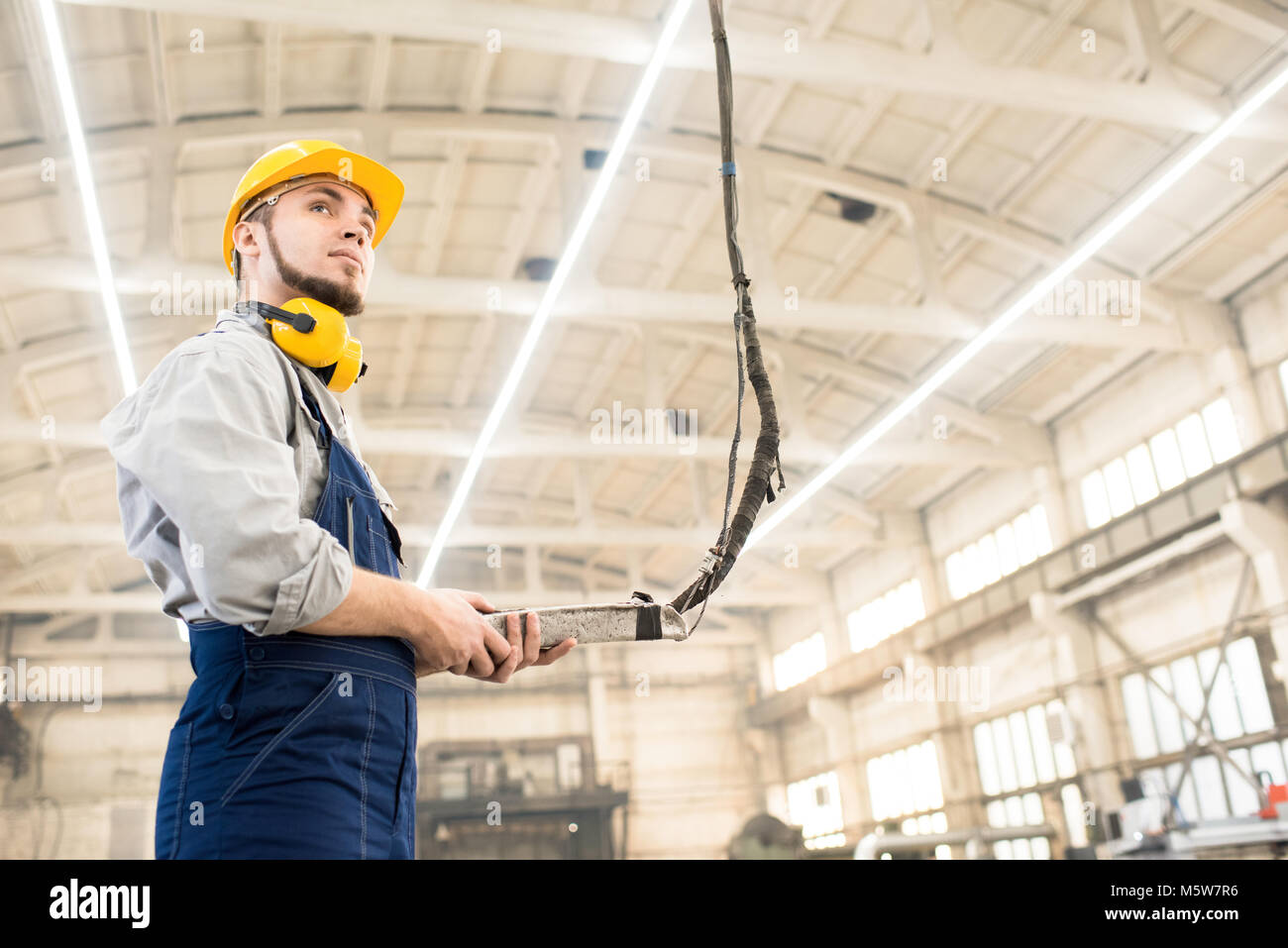 Low angle view of bearded machine operator wearing overall and protective helmet wrapped up in work while standing - Stock Image