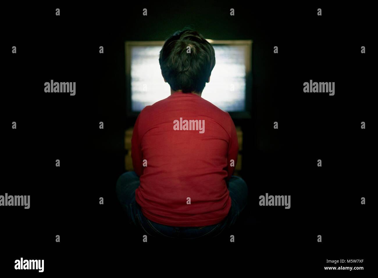boy watching TV on black background - Stock Image