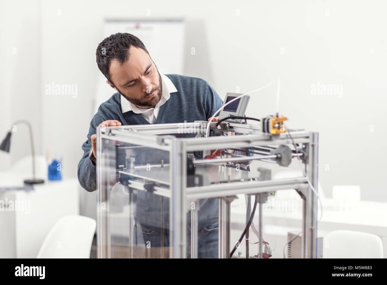 Pleasant young man checking the work of 3D printer - Stock Image