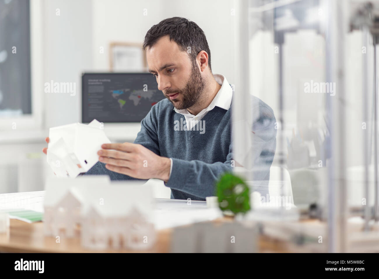 Handsome engineer checking 3D model of house - Stock Image